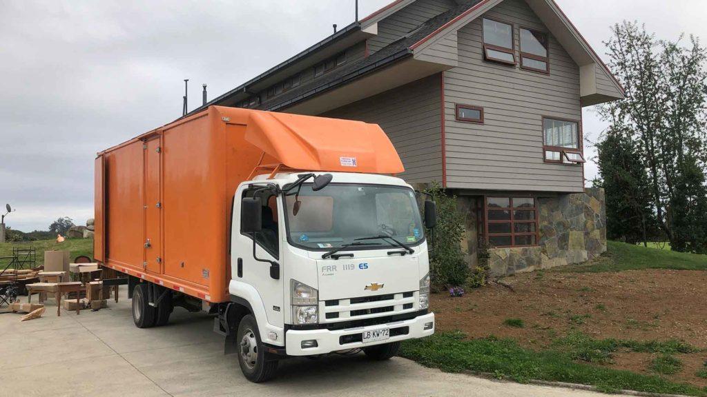 camion con carroceria naranja estacionado a un lado de una casa gris