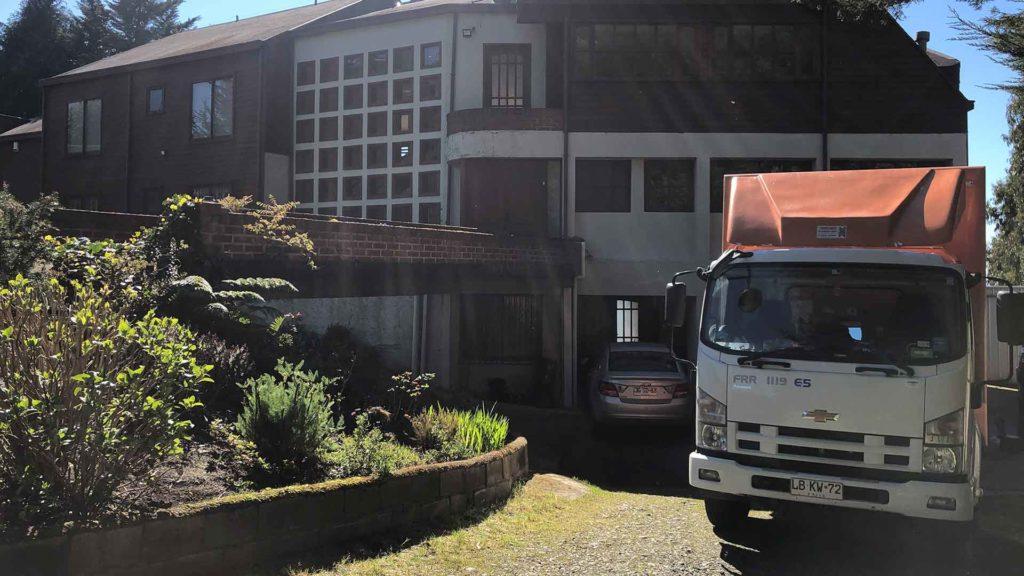 Casa grande con un auto estacionado en el porsche y un cambio afuera