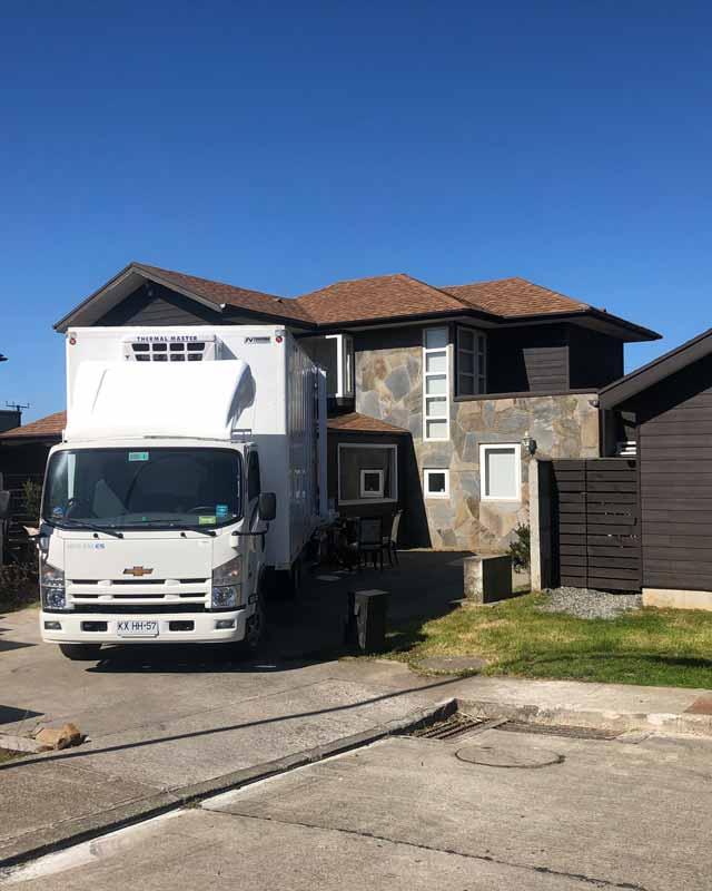 camion de color blanco estacionado afuera de una gran casa de dos pisos