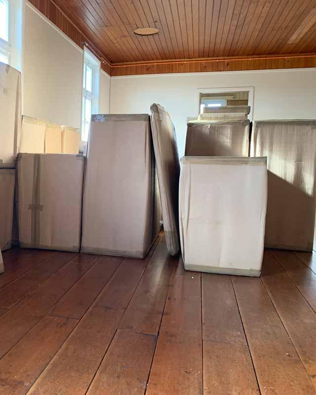 varios muebles embalados en carton dentro de un cuarto vacio