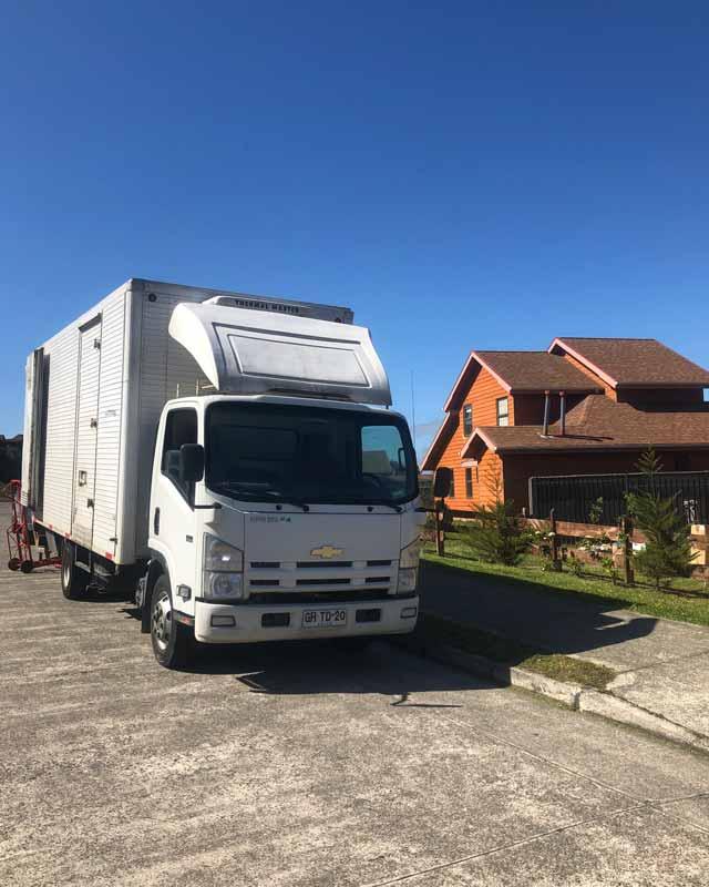 camion de mudanzas blanco estacionado en la calle y una casa al lado de 2 pisos