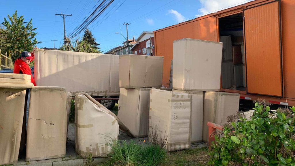 Muebles embalados frente a camion naranjo